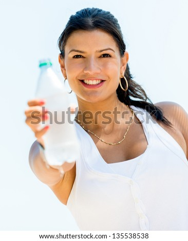 Healthy woman drinking water from a bottle and smiling