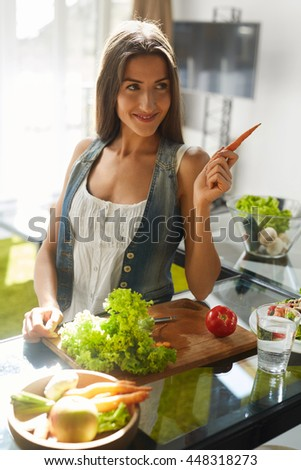 Healthy Woman Eating Vegetables In Kitchen. Beautiful Happy Smiling Girl With Fit Body Cooking Fresh Organic Vegan Salad, Preparing Detox Food To Eat. Fitness Diet, Weight Loss Nutrition Concept
