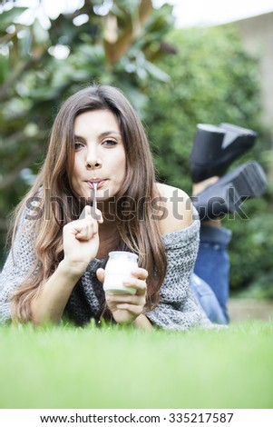 Healthy woman eating yoghurt on spoon.