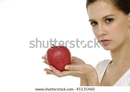 Healthy woman is holding an red apple in front of her smiling face