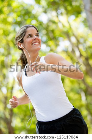 Healthy woman jogging outdoors looking very happy - stock photo
