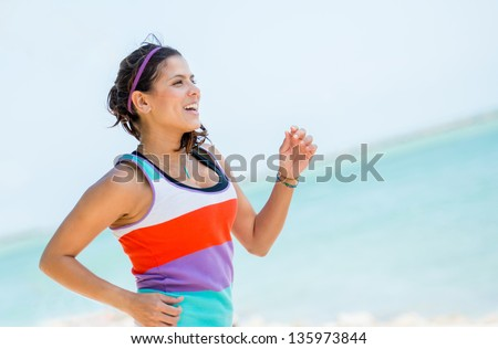 Healthy woman running outdoors looking very happy - stock photo