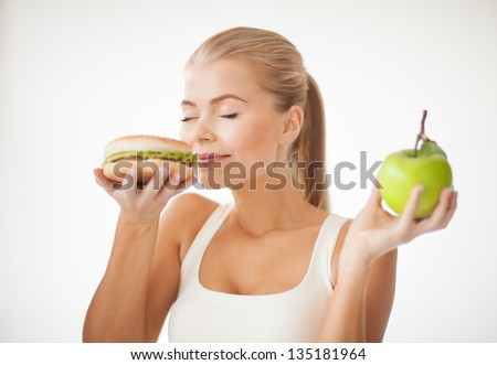 healthy woman smelling hamburger and holding apple