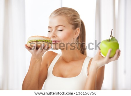 healthy woman smelling hamburger and holding apple - stock photo