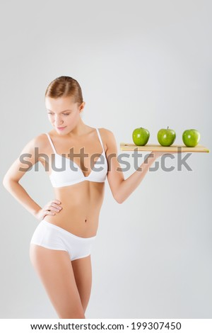 Healthy woman stands with green apple. Healthy eating concept. - stock photo
