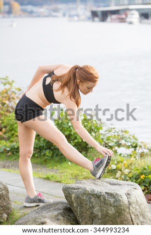 Healthy woman stretching before an outdoor run - stock photo