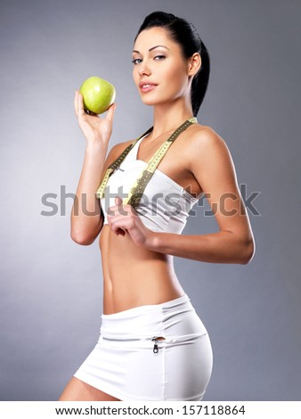 Healthy woman with apple after diet. Sporty female with perfect figure