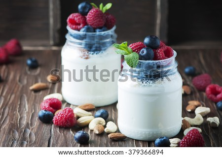 Healthy yogurt with belly and nuts, selective focus - stock photo