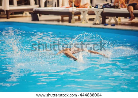 Healthy young adult male aquatic athlete. Professional swimmer in blue water swimming pool, Happy young man having fun  swimming pool. - stock photo