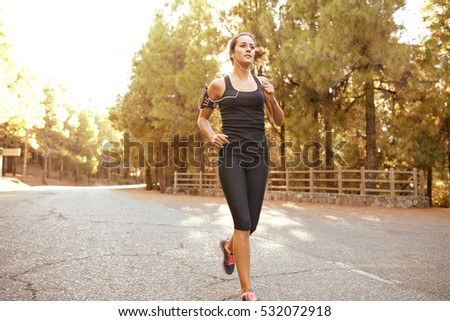 Healthy young brunette woman out jogging alone on a tarred road surrounded with a forest of trees and over exposed sunlight