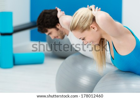 Healthy young couple doing Pilates exercises together in the gym shaping and toning their muscles while doing balancing exercises on gym balls - stock photo