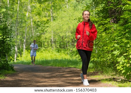 healthy young female athlete running in a summer park smiling and happy while working out