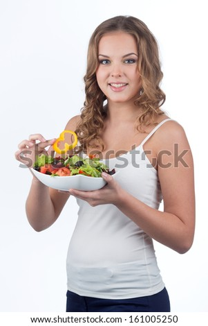 Healthy young girl eats delicious vegetable salad