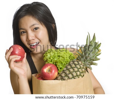 Healthy young girl holding a bag of groceries and an apple