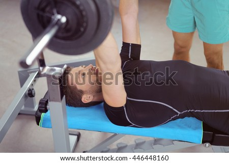 Healthy young male bodybuilder lifting weights on a bench raising a barbell above his body with a fitness instructor standing by - stock photo