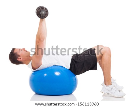 healthy young man exercising using a fitness ball and dumbbells on white background