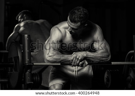 Healthy Young Man Resting In Healthy Club Gym After Exercising - stock photo