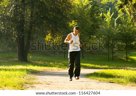 healthy young man running in the morning in the park - stock photo