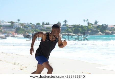 Healthy young man running on the beach in summer - stock photo