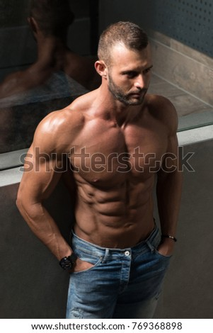 Healthy Young Man Standing Strong Standing On Stairs and Flexing Muscles - Muscular Athletic Bodybuilder Fitness Model Posing After Exercises - a Place for Your Text