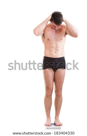 Healthy young man with a weight scale. Isolated over white background - stock photo