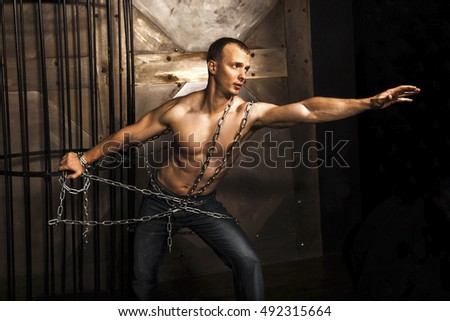 Healthy young man with strong muscular arms and torso pulling the chain. Cage.  Fitness concept