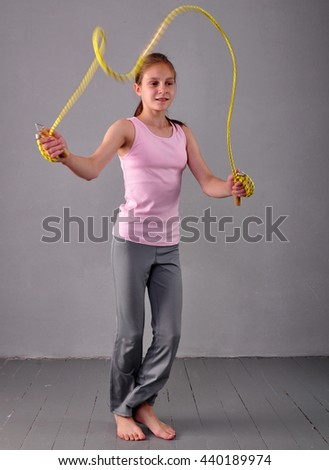 Healthy young muscular teenage girl skipping rope in studio. Child exercising with jumping on grey background. Sport healthy lifestyle concept. Sporty childhood. - stock photo