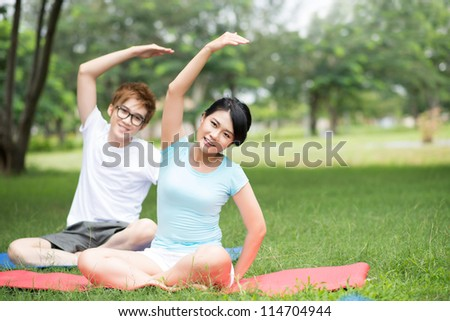 Healthy young people doing stretching exercises simultaneously - stock photo