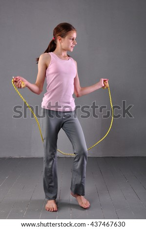 Healthy young teenage girl skipping rope in studio. Child exercising with jumping high on grey background. Sport healthy lifestyle concept. Sporty childhood. - stock photo