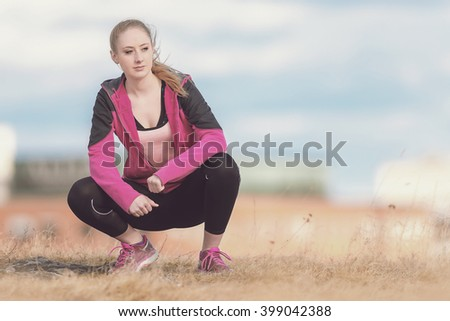 Healthy young woman before running in city park. Cropped version in toned colors. - stock photo
