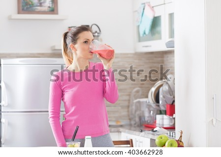 Healthy young woman drinking a fruit smoothie in her kitchen.