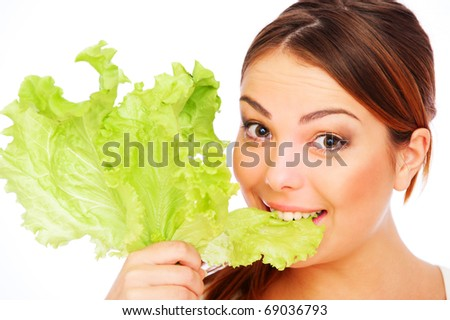 healthy young woman eating green lettuce over white background - stock photo