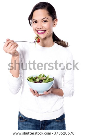 Healthy young woman eating green salad over white