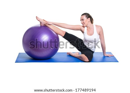 healthy young woman exercising with fit-ball in gym