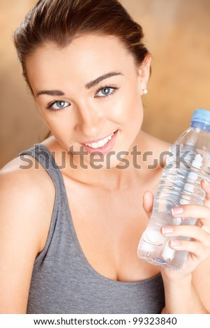 Healthy young woman holding a bottle of water and smiling - stock photo