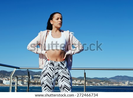Healthy young woman in sportswear relaxing after a jog while standing on wooden pier of beautiful beach,female runner taking break after fitness training outdoors while standing with hands on her hips - stock photo