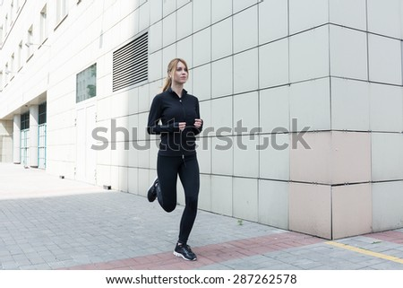 Healthy young woman is runing in the city - stock photo
