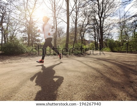 Healthy young woman jogging in park. Fitness female model running in forest. Caucasian fitness model exercising outdoors. - stock photo
