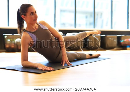 Healthy Young Woman Laying on her Side on a Fitness Mat and Doing Leg Exercise at the Gym While Looking Into Distance. - stock photo