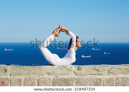 Healthy young woman makes yoga on high altitude with beautiful sea with ships on background, attractive woman practicing yoga enjoying sunny day at summer, yoga with amazing view of sea from high - stock photo