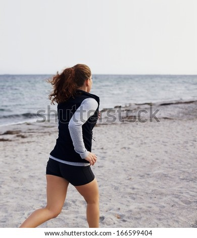 Healthy young woman running on seashore. Young caucasian female model jogging on beach outdoors. Female runner training on sandy beach. - stock photo