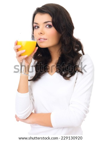 Healthy young woman sipping fresh orange juice from an elegant stemmed glass while looking sideways at the camera   over white - stock photo