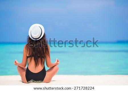 Healthy young woman sitting in yoga position meditating on the beach - stock photo