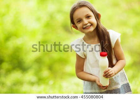 Healthy, yummy childhood concept. Portrait of funny and sweet little girl outdoors with long hair in the wind, milk mustache on face. Copy-space