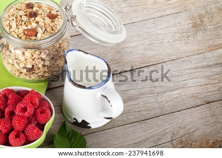 Healty breakfast with muesli, berries and milk. View from above on wooden table with copy space - stock photo