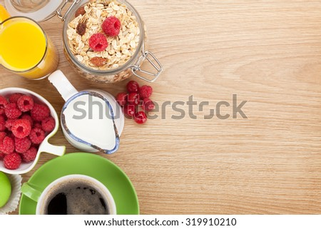 Healty breakfast with muesli, berries, orange juice, coffee and croissant. View from above on wooden table with copy space - stock photo