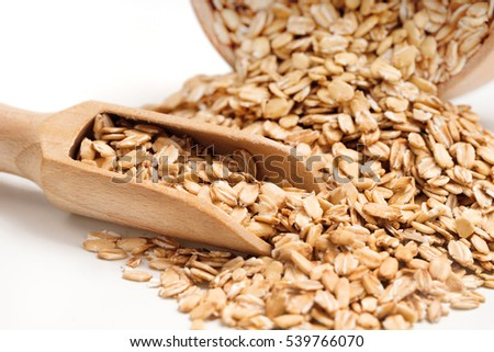 Heap oat flakes and scoop on white background. Healthy food. Close up, high resolution product.