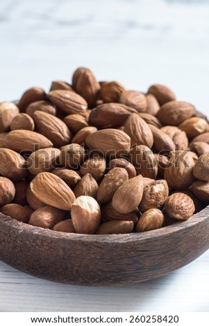 Heap of almonds in the wooden bowl,selective focus - stock photo