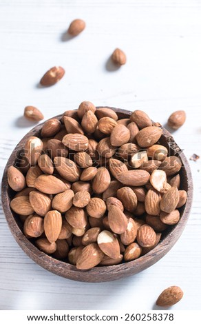 Heap of almonds in the wooden bowl,selective focus and blank space - stock photo
