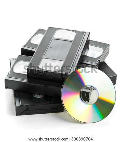 Heap of analog video cassettes with DVD disc - old movies backup or transfer concept - stock photo